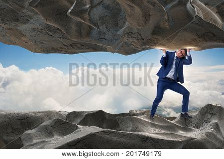Businessman supporting stone under pressure