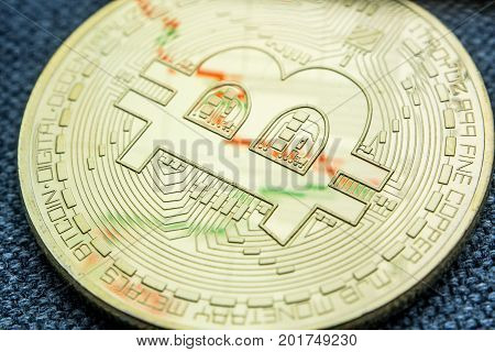 Golden Bitcoin Coin With A Chart Reflection On Its Surface