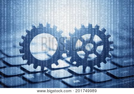 Two gears on computer keyboard with computer code in the background