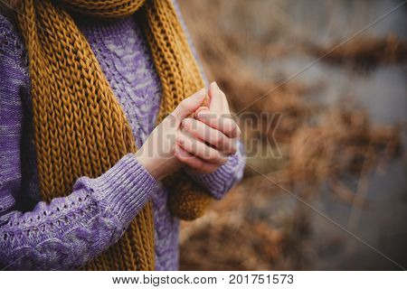 Fall sadness background. Unrecognisible girl in lilac knitted sweater and ocher scarf warming her hands close up.