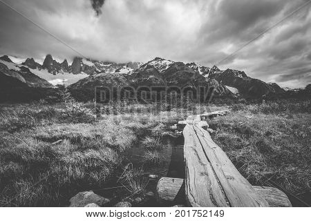 Black and white picture of the bridge over the swamp. A wooden platform over the swamp. Landscape of mountains with clouds in the afternoon. Snow-capped mountain tops are shrouded in clouds.