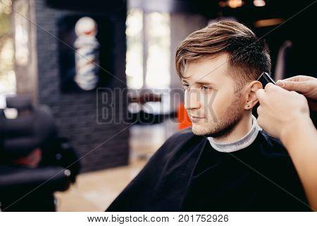 Man in barber shop men's hairdresser. Hairdresser does haircut