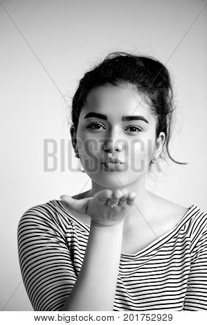 Cute lovely young woman standing and sending kiss over white background. Flying Kiss, Woman in Love .