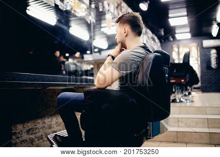 Man is sitting in a barber's chair barber shop. Back view