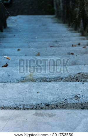 historic concrete stair downside view with cigarette on floor dirty