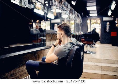 Man is sitting in a barber's chair barber shop.