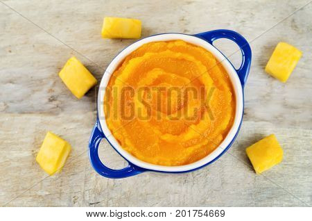 Pumpkin puree with raw slices on a wood background