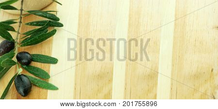 Black olives and olive tree branch on wooden background