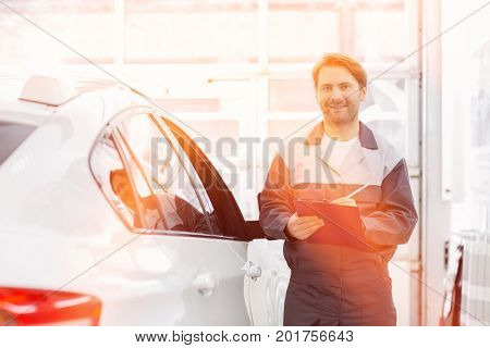 Portrait of smiling male automobile mechanic holding clipboard while standing by car in repair shop