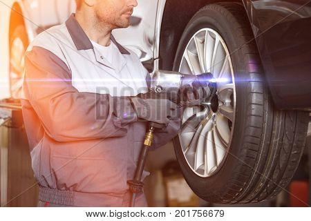 Midsection of male mechanic repairing car's wheel in workshop