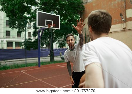 Sports hobby activity leisure and healthy lifestyle concept. Team of basketball fans playing streetball game at open outdoor court on sunny summer day bearded brunette man teasing his rival