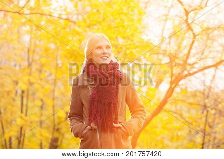 Thoughtful woman in jacket looking away at park during autumn