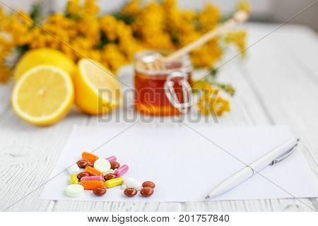 Honey and lemon. Many pills and vitamins. Letter to the recipe and pen. Concept illness colds cure fall and winter.