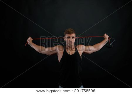 Hardworking young male athlete exercising in gym using rubber band building muscles in the upper and lower arm standing against black wall background with copy space for your promotional content