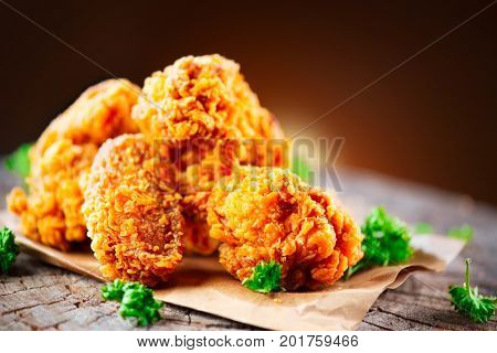 Fried chicken wings and legs on wooden table. Breaded Crispy fried kentucky chicken tasty dinner. Close up of tasty and juicy fried chicken