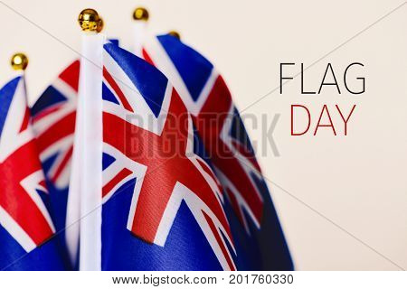 closeup of some australian flags and the text flag day against an off-white background