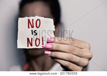 closeup of a young caucasian woman with pink polished nails holding a piece of paper with the text no is no written in it, in front of her face
