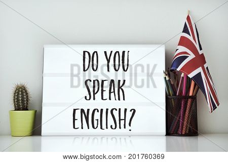 a lightbox with the question do you speak English? written in it, a cactus, a pot of pencils and a flag of the United Kingdom on a white table, against a white background
