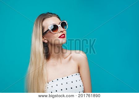 Summer Model Portrait. Dressed Well Stylish Girl On Sunglasses On Blue Turquoise Background. Cheerfu