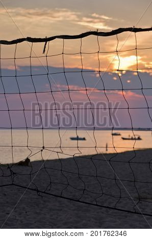 Sunset at Toroni beach through old volleyball net in Sithonia, Greece