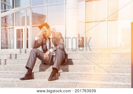Full length of depressed businessman sitting on steps outside office