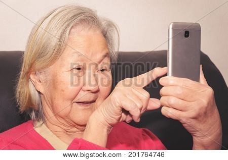 Old Woman Holding A Smartphone And Touching The Screen