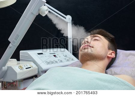 Face steaming, young man. Caucasian guy in beauty clinic. Facial steaming benefits.