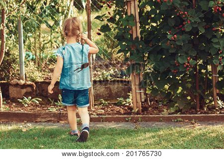 Young girl is ready for hoeing garden with small hoe.