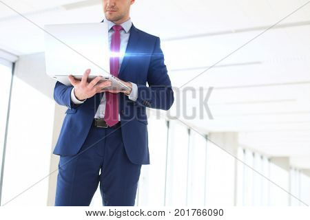 Midsection of young businessman using laptop while standing in new office