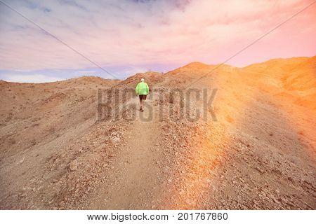 Rear view of senior man jogging on mountain