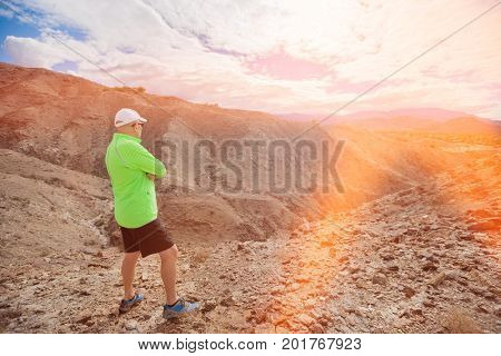 Full length of senior man looking at view while standing on rock