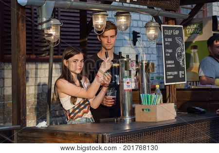 KYIV, UKRAINE - JUL 23, 2017: Young saleswomen pours cold beer from keg at the counter of Street Food Festival on July 23, 2017. Kiev is the 8th most populous city in Europe.
