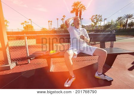 Tired senior tennis player relaxing on bench at court