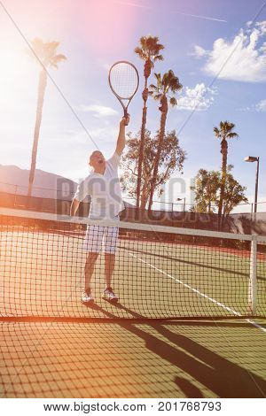 Senior male tennis player playing on court
