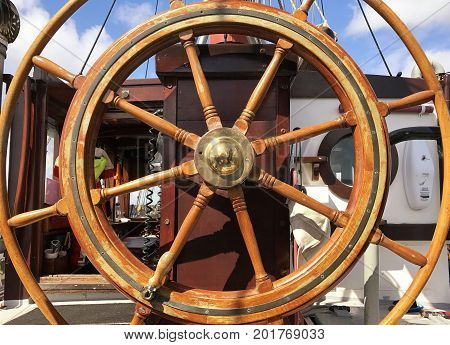 Close up of the helm of a yacht with the blue sky showing through the steering wheel. With space for text.