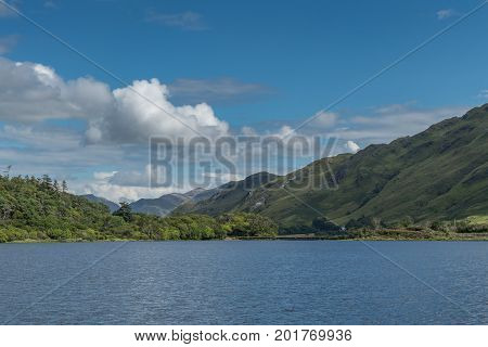 Connemara Ireland - August 4 2017: Looking East over Pollacapall Lough from the grounds of Kylemore Abbeys shows blue water a dam blue sky with white clouds and forested green hills.