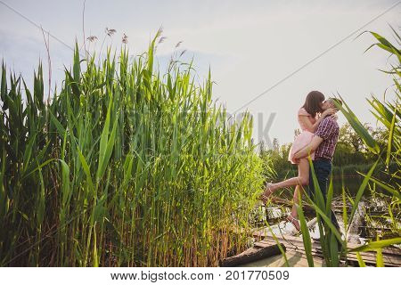 Lovers In A Lake. Young Couple In Love Sitting On The Park Ground Near The Water While These Young M
