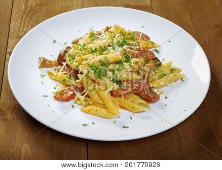 Italian Penne rigate pasta with sausage perish close up meal