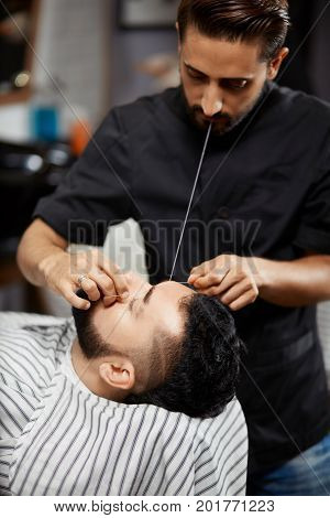 Professional hairdresser in black doing coraction of bread and mustache for brunet man, who sitting at cozy chair in stylish barber shop. Handsome stylist doing hair removal with thread.