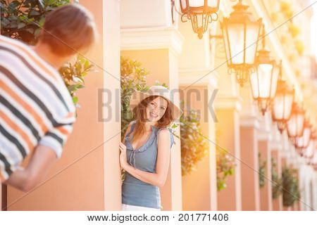 Happy woman playing hide-and-seek with man amongst pillars