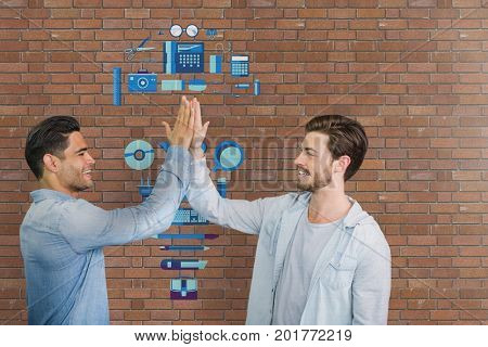 Digital composite of Happy business men doing a high five against brick wall with graphics