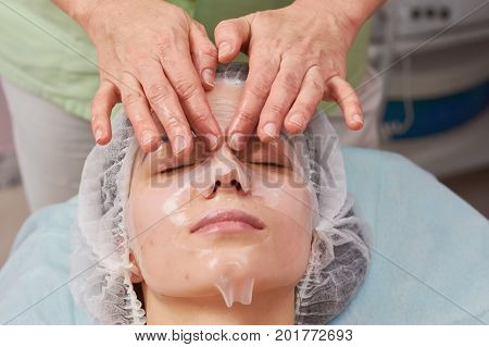 Hands applying collagen face mask. Work of cosmetician. Keeping skin hydrated.