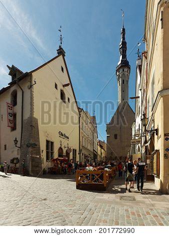 TALLINN, ESTONIA - JUNE 10, 2017: People resting on Vana turg against Town Hall tower. The Old Town is one of the best preserved medieval cities in Europe and is listed as a UNESCO World Heritage Site