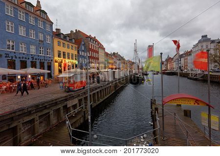 COPENHAGEN, DENMARK - NOVEMBER 6, 2016: People walking and resting in evening Nyhavn. It is lined by brightly colored 17th and early 18th century townhouses and bars, cafes and restaurants