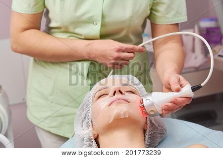 Girl undergoing cosmetic therapy. Hydrogel mask, rf skin tightening.