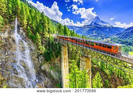 Zermatt Switzerland. Gornergrat tourist train with waterfall bridge and Matterhorn. Valais region.