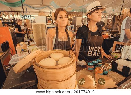 KYIV, UKRAINE - JUL 23, 2017: Two beautiful saleswomen selling dim sum asian food at popular outdoor Street Food Festival on July 23, 2017. Kiev is the 8th most populous city in Europe