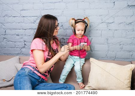Mom and daughter listen to music in big headphones put on their head, sitting on the sofa in the interior. Holds the phone.
