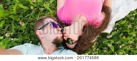 Summer, love and people concept - happy teenage couple in sunglasses lying on grass and taking selfie on smartphone.