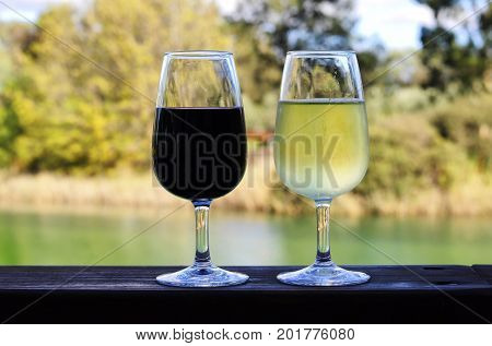 Two Glasses Of Red And White Wine On Wooden Rail